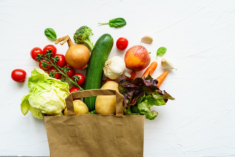 a grocery bag overflowing with vegetables