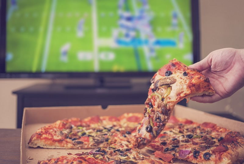 a person eating pizza out of a takeout box as they watch football