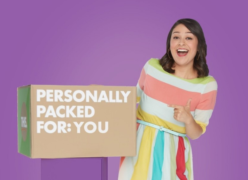 a smiling woman pointing to a meal delivery package