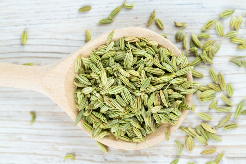 fresh fennel seeds in a large wooden spoon