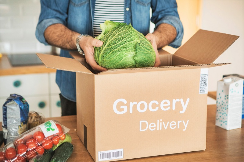 : Man unpacking a cabbage from an online grocery delivery box