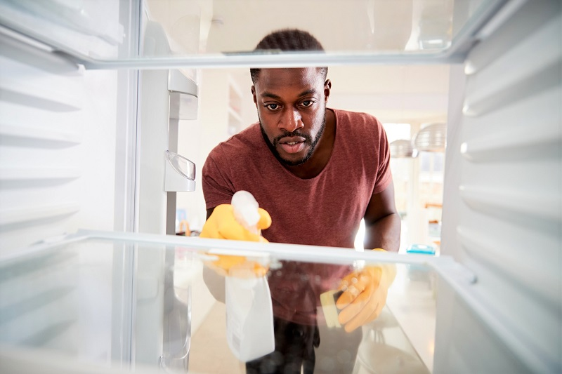 man spring cleaning the inside of his kitchen refrigerator