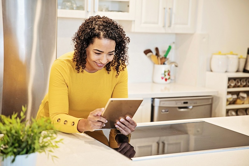 Woman leaning on kitchen counter while looking at a tablet