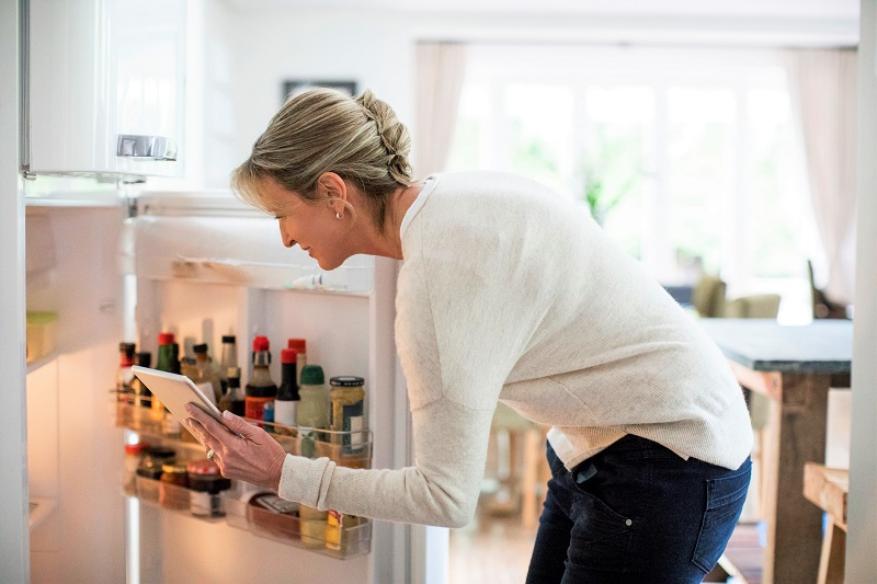 Woman standing in front of the open refrigerator, writing down a grocery list.