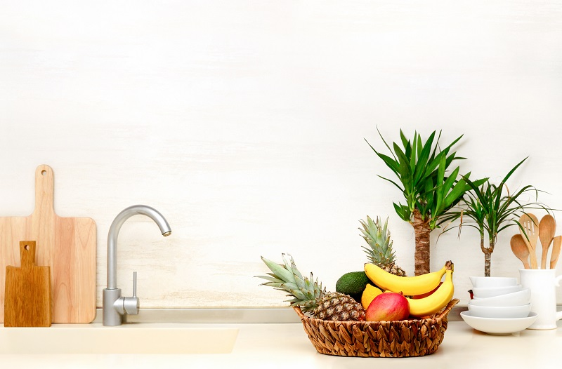 a well-organized kitchen sink with a wicker basket full of fruit