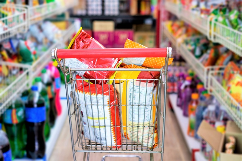 Shopping cart in supermarket aisle, filled with junk food.