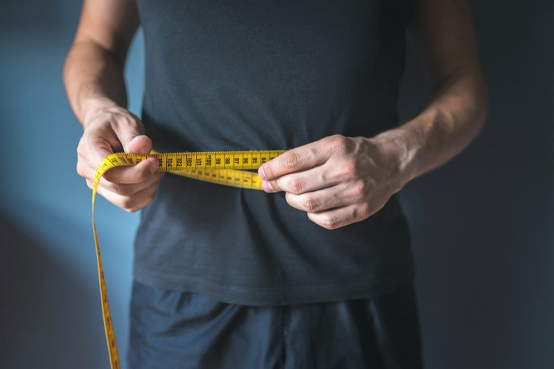 a man measuring the circumference of his waist with a measuring tape