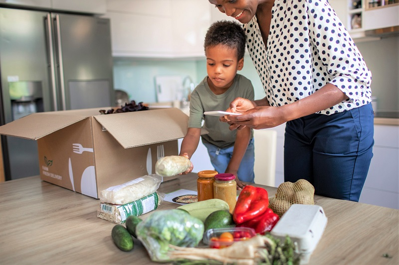 Woman and Boy unpacking groceries from a box