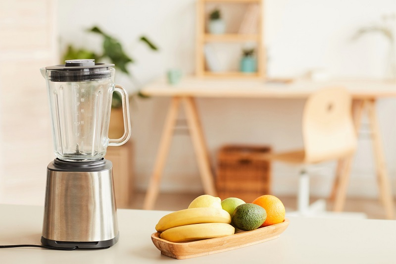 a kitchen display with a blender and a collection of fruits on a wooden bowl