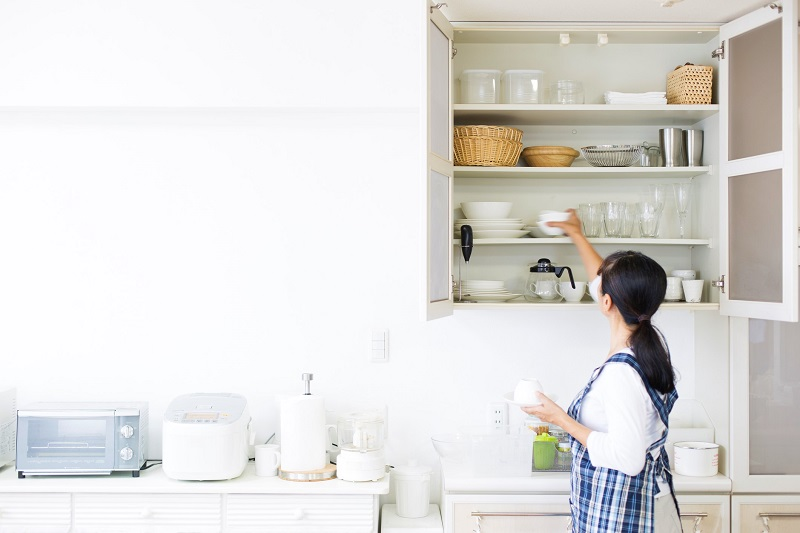a woman looking at her kitchen cabinet organization