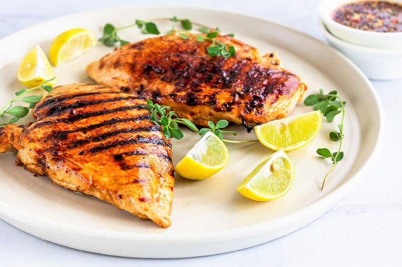 Grilled Balsamic Chicken Breast on a plate with lemon and oregano