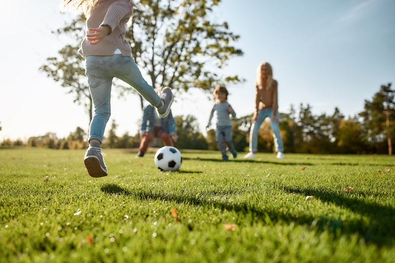 family playing soccer outside