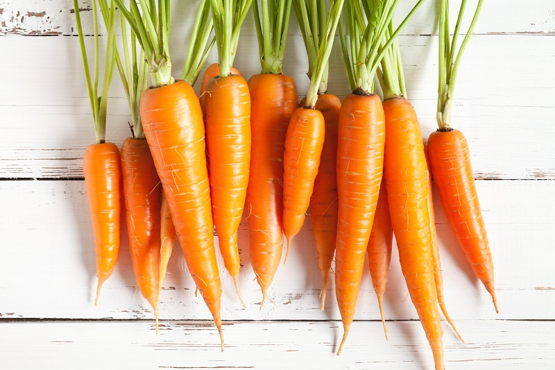 fresh carrots on a white wooden table