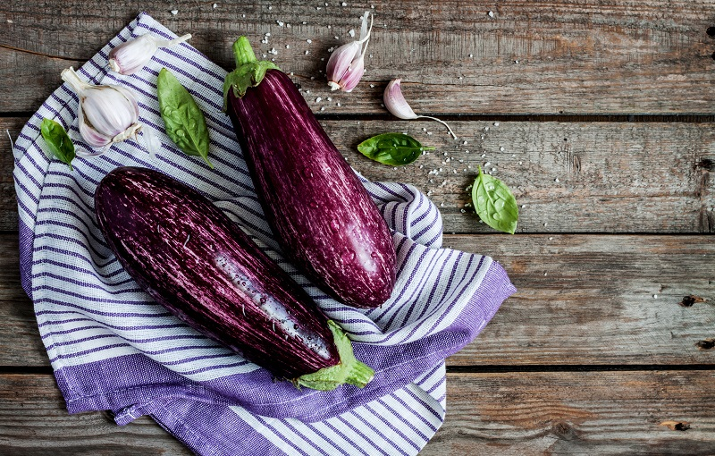 two fresh eggplants on a wooden table
