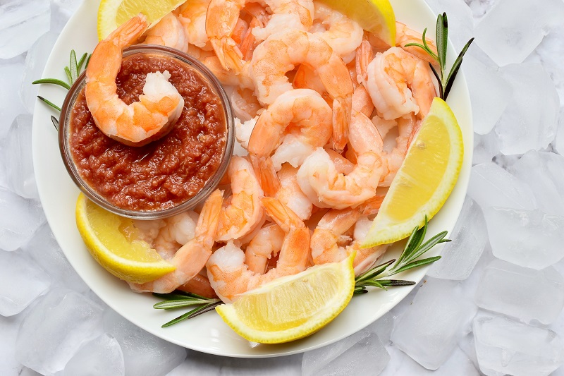 shrimp cocktail with lemon wedges and thyme