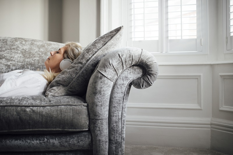 a woman resting on a gray couch with her headphones on for stress relief
