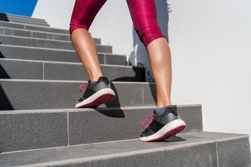 Legs of a woman walking up the stairs to burn more calories