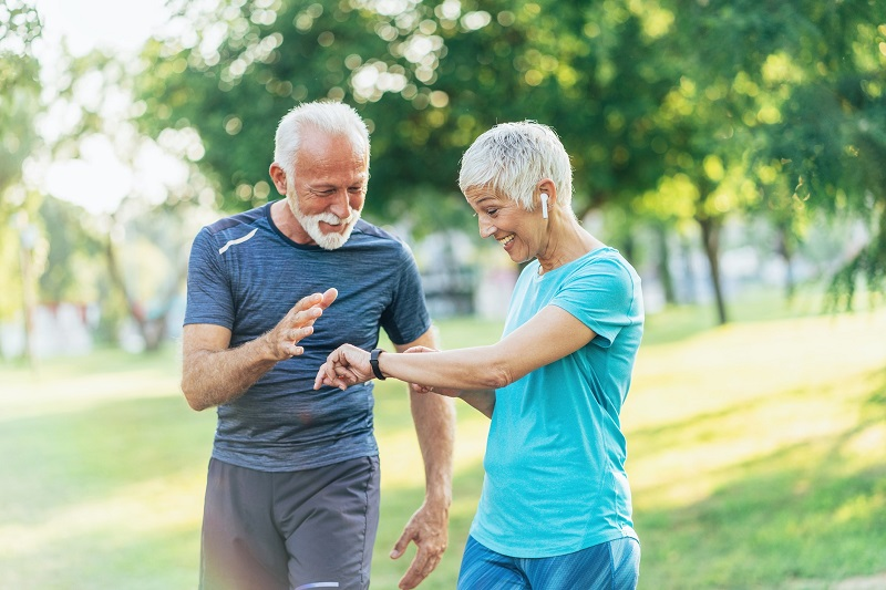 Older man and woman in a park setting their activity trackers while walking to burn more calories