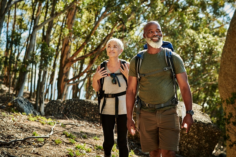 man and woman walking in the woods to burn more calories
