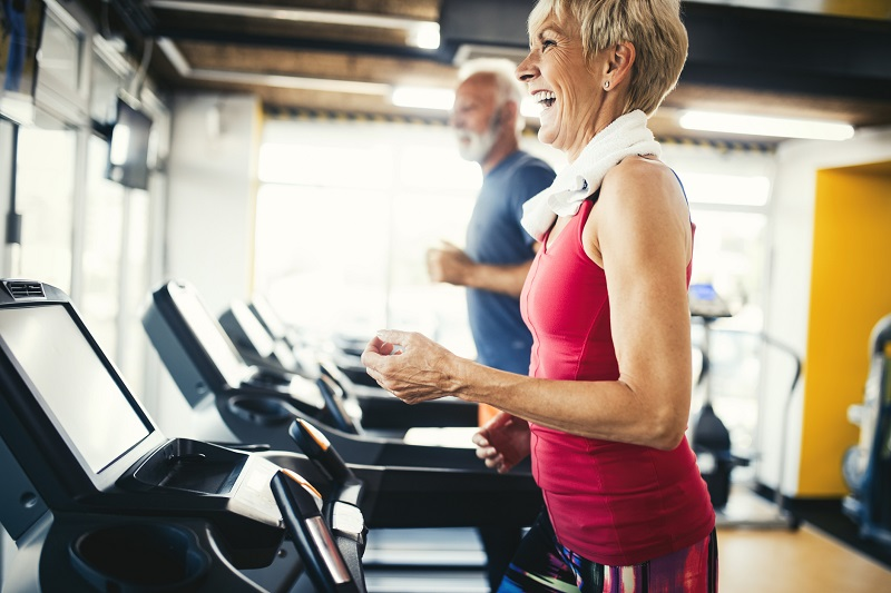 man and woman walking on a treadmill to burn more calories