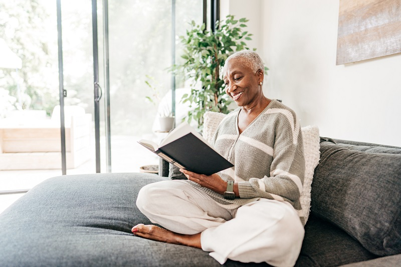Woman sits cross-legged on her bed by the windows, smiling as she holds an open book