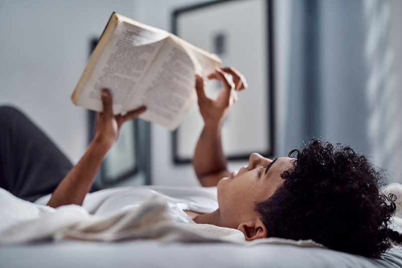Young man reads a book as though he is staring at the stars and dreaming