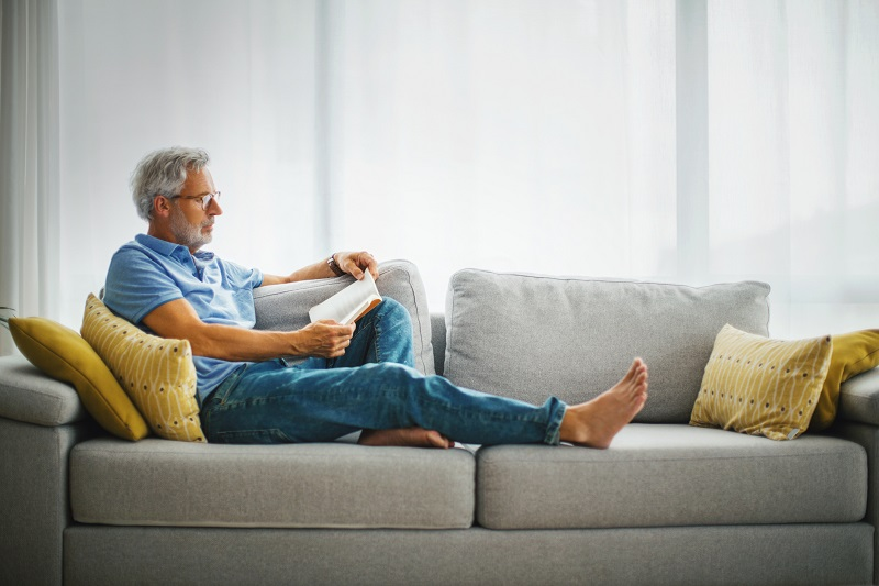 An older man, stretched on a couch, wears glasses as he reads a book