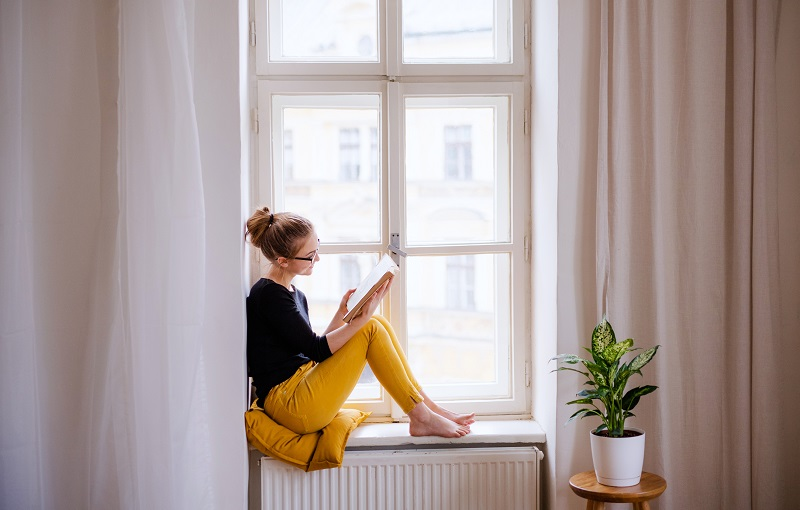 Woman perched on her windowsill, reading a book in the natural daylight