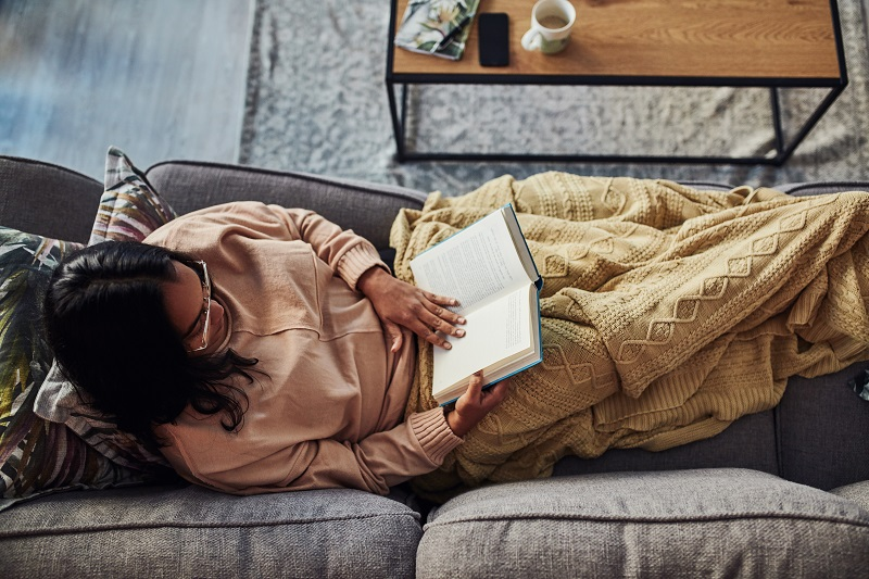 Woman reclines on couch, wrapped in a blanket, reading her book
