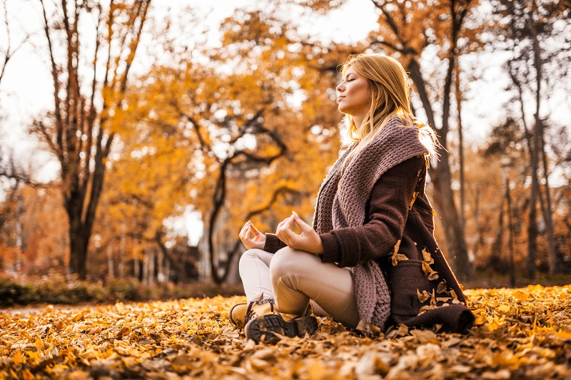 Self-care for this woman is meditating on the ground, surrounded by yellow leaves and trees